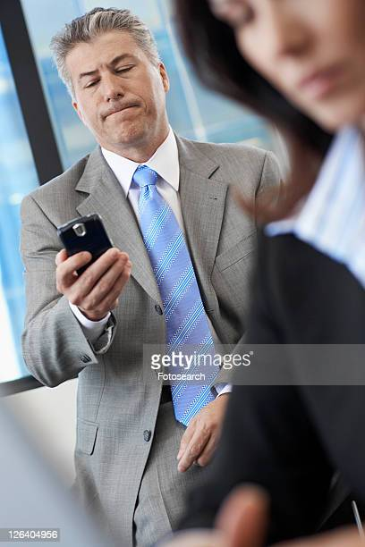 Businessman checking mobile phone near colleague