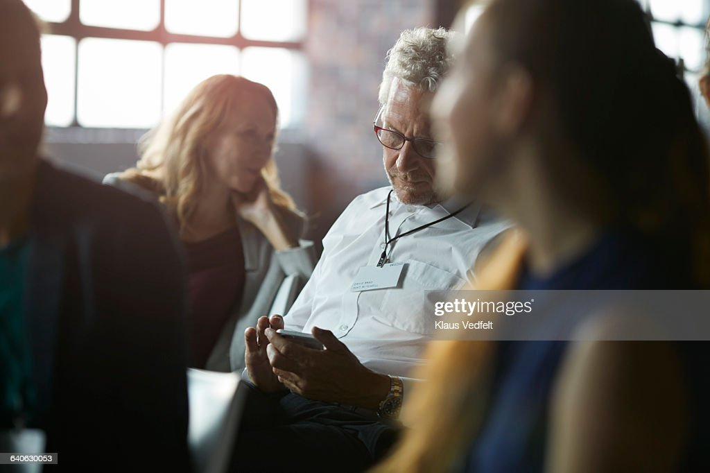 Businessman checking phone among colleagues