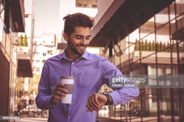 Homme d'affaires contrôle le temps à l'extérieur. Homme regardant montre.
