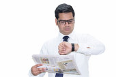 Businessman reading newspaper and checking the time on wristwatch