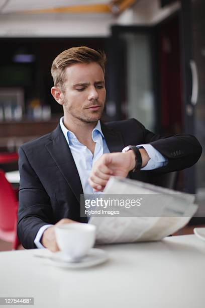 Businessman checking time at breakfast