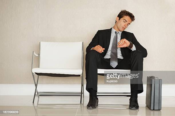 Businessman checking time while waiting