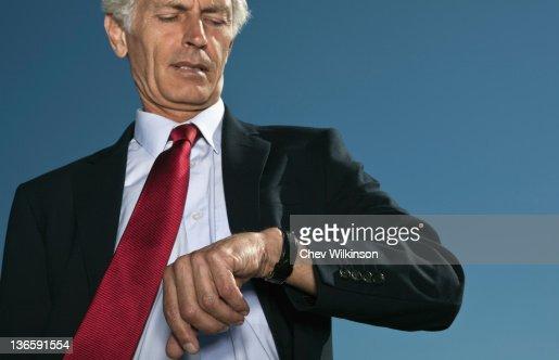 Businessman checking watch outdoors : Bildbanksbilder