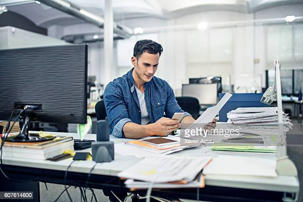 Businessman checks documents while on the mobile phone