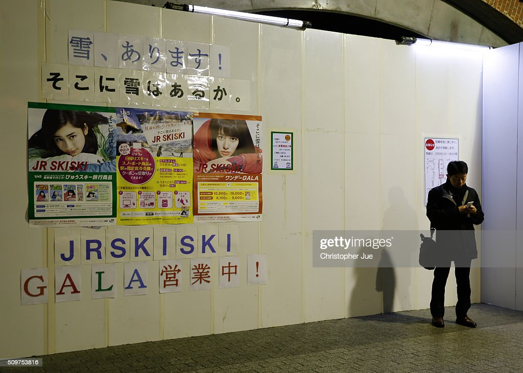 A businessman checks his mobile phone in downtown Tokyo on February 12, 2016 in Tokyo, Japan. The Nikkei Stock Average finished 11% down for the week, its biggest weekly drop since October 2008, and the index for the day ended 4.8% down, the lowest since October 2014.