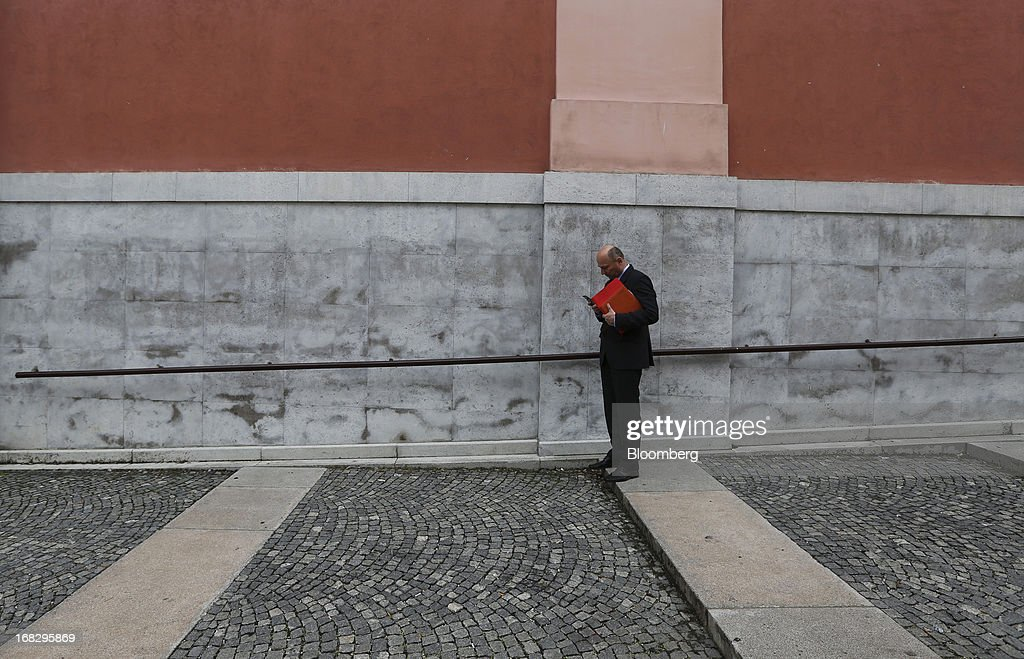 A businessman checks his mobile phone on a street in Ljubljana, Slovenia, on Tuesday, May 7, 2013. Slovenia plans to increase taxes to make up for the swelling budget shortfall as the country works to recapitalize its banks. Photographer: Chris Ratcliffe/Bloomberg via Getty Images