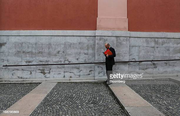 A businessman checks his mobile phone on a street in Ljubljana Slovenia on Tuesday May 7 2013 Slovenia plans to increase taxes to make up for the...