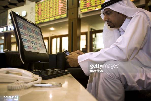 A businessman checks his Research In Motion Ltd BlackBerry handset at the Dubai Financial Market trading floor in Dubai United Arab Emirates on...