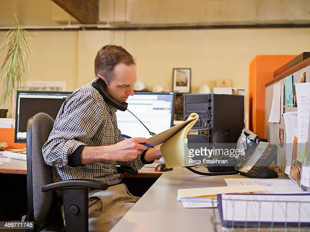 Businessman checks notes while on the phone