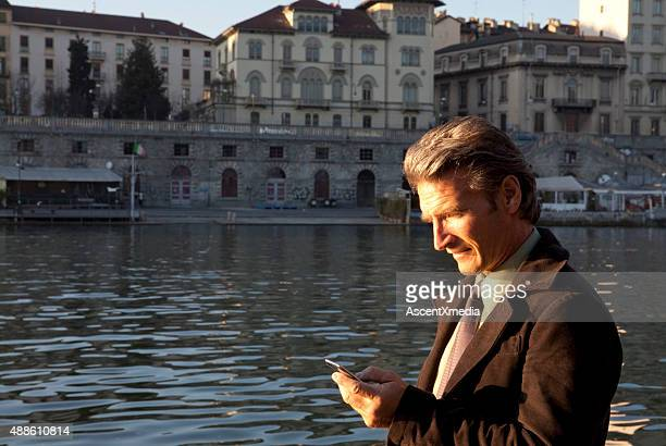 Businessman checks text, at riverside, sunrise