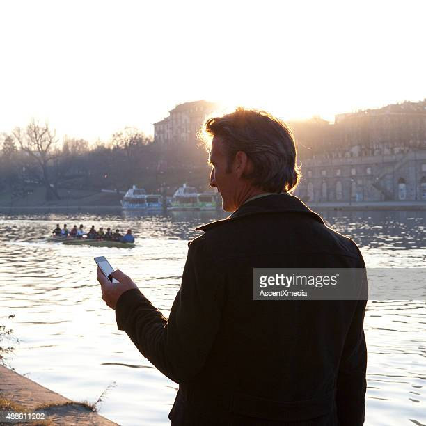 Businessman checks text, rowers on river, sunrise