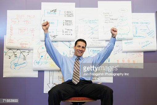 Businessman cheering in front of wall charts : Stock-Foto