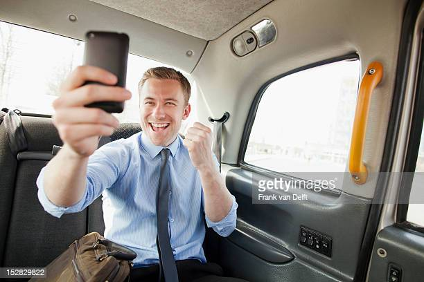 Businessman cheering on cell phone