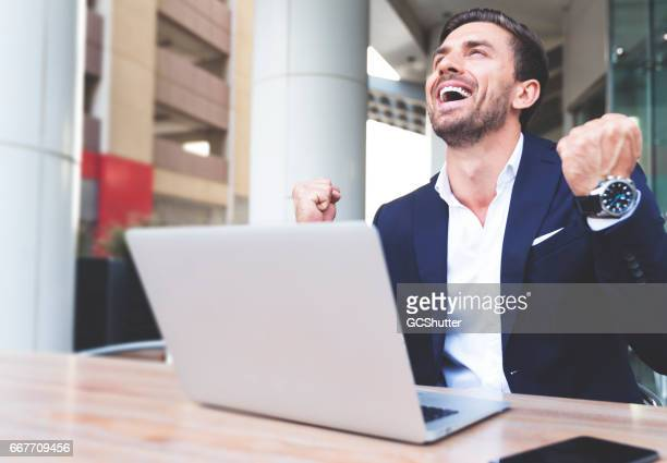 Businessman cheering with excitement while working on his laptop