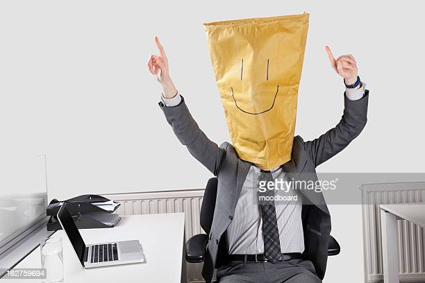 Businessman cheering with smiley drawn on paper bag over face in office