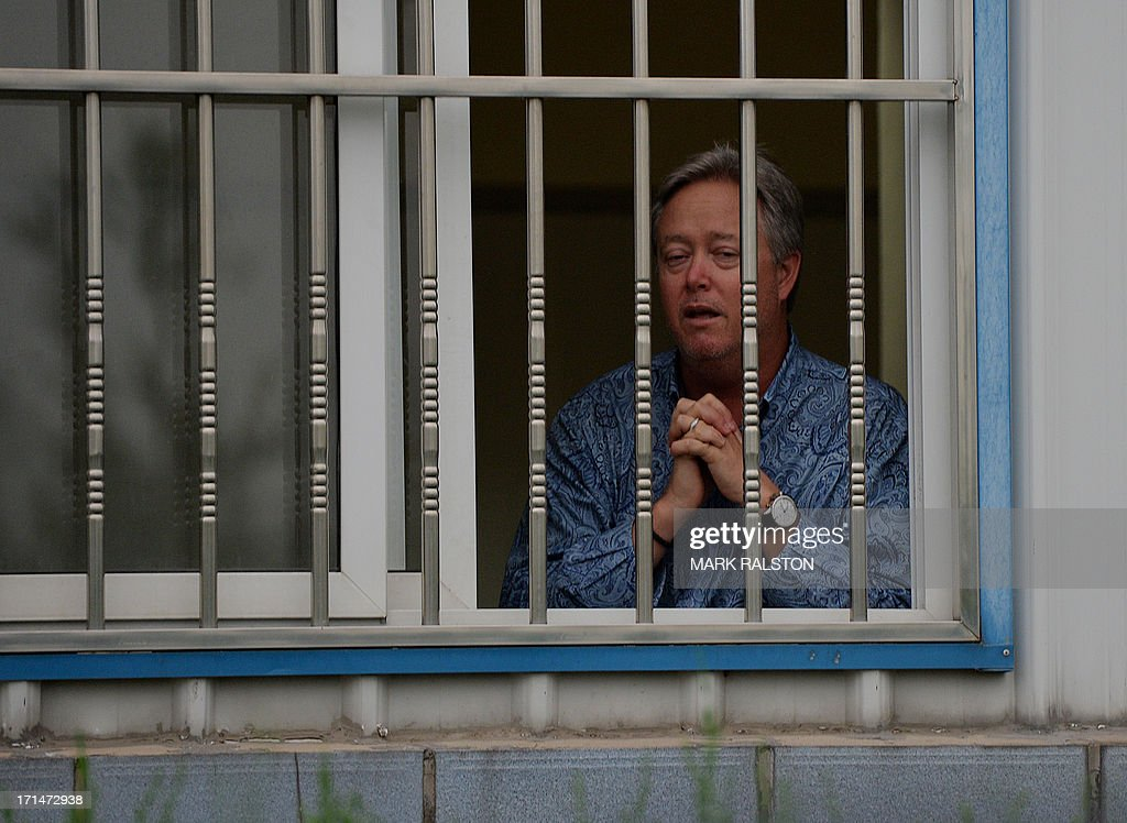US businessman Chip Starnes stands behind the bars of his office window after being held hostage for five days over a wage dispute at his Specialty Medical Supplies factory in Huairou, Beijing on June 25, 2013. Starnes, who had come from the US-based company to lay off 30 employees, said the remaining 100 then barred him from leaving until they reached a resolution. AFP PHOTO/Mark RALSTON
