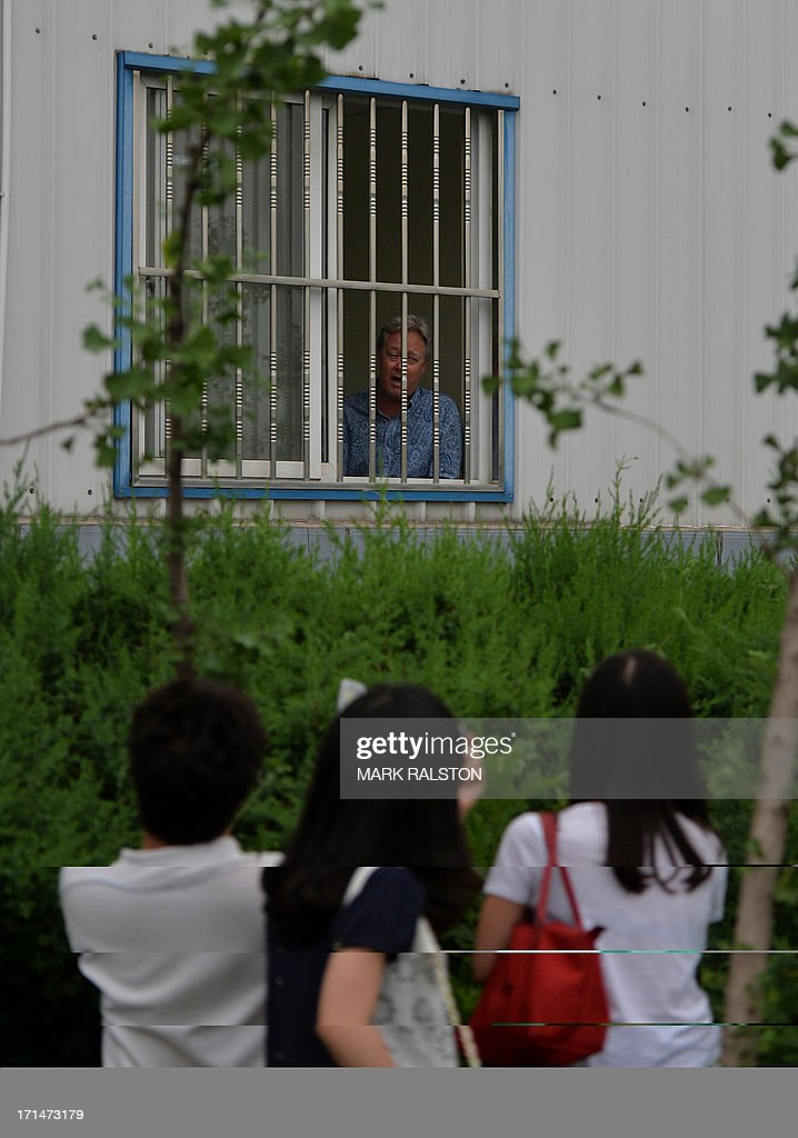US businessman Chip Starnes (top C) stands behind the bars of his office window after being held hostage for five days over a wage dispute at his Specialty Medical Supplies factory in Huairou, Beijing on June 25, 2013. Starnes, who had come from the US-based company to lay off 30 employees, said the remaining 100 then barred him from leaving until they reached a resolution. AFP PHOTO/Mark RALSTON