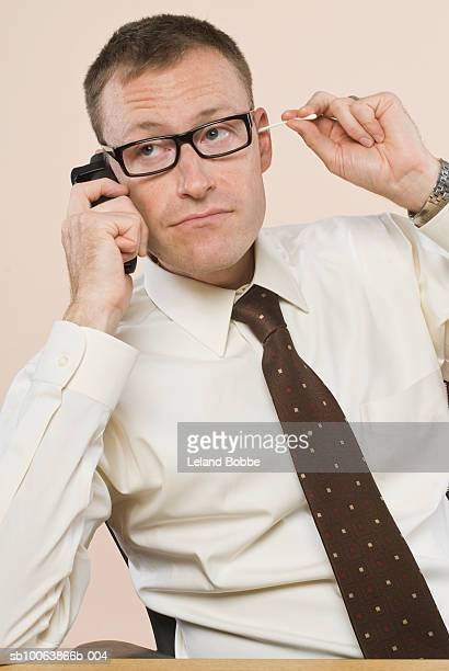 Businessman cleaning ear and using mobile phone, close-up