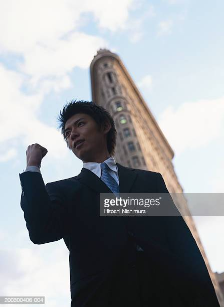 Businessman clenching fist outdoors, low angle view