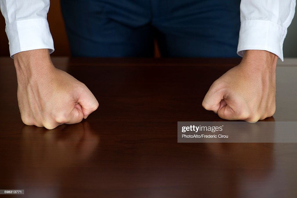 Businessman clenching fists, cropped