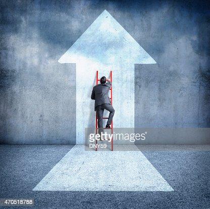 Businessman climbing ladder towards success