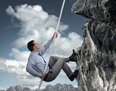 Business man climbs a mountain concept for challenge, conquering adversity and leadership