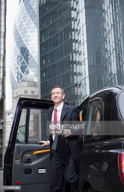 Businessman climbing out of taxi cab