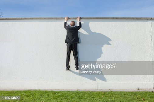 Businessman climbing over wall