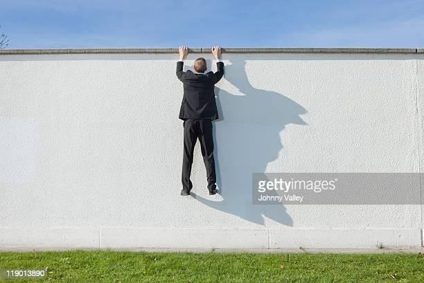 Geschäftsmann Klettern über Mauer