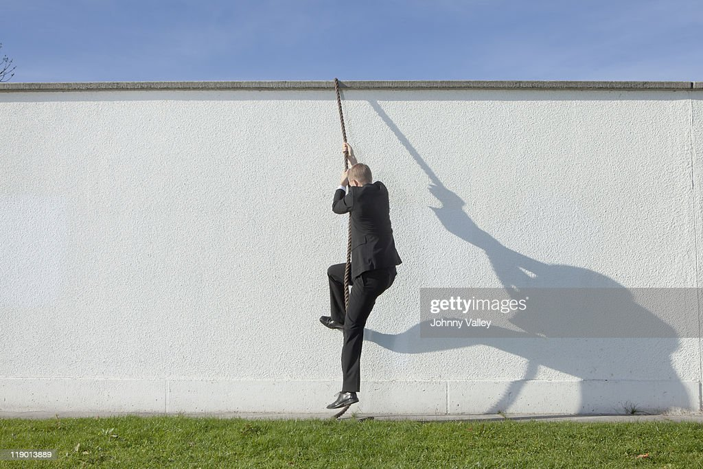 Businessman climbing over wall with rope : Stock Photo