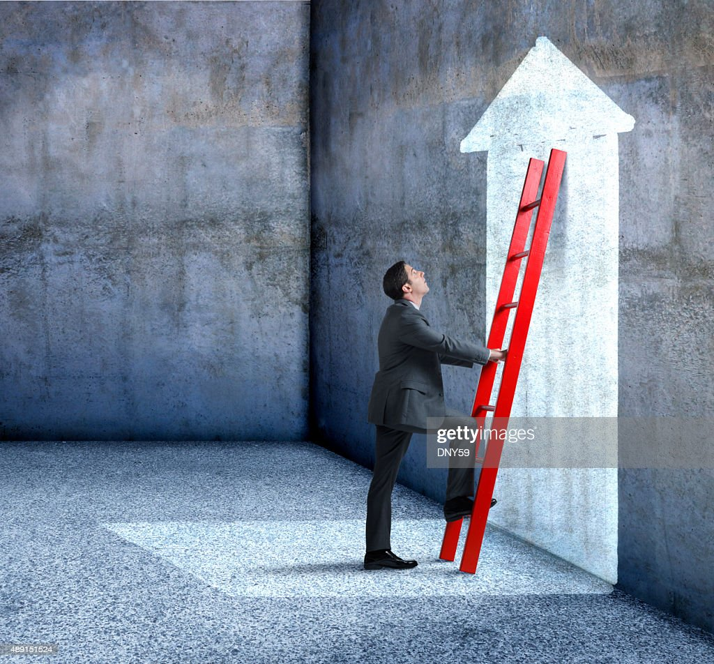 Businessman Climbing Red Ladder Leaning Against Wall With Arrow : Stock Photo