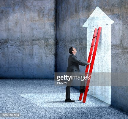 Businessman Climbing Red Ladder Leaning Against Wall With Arrow