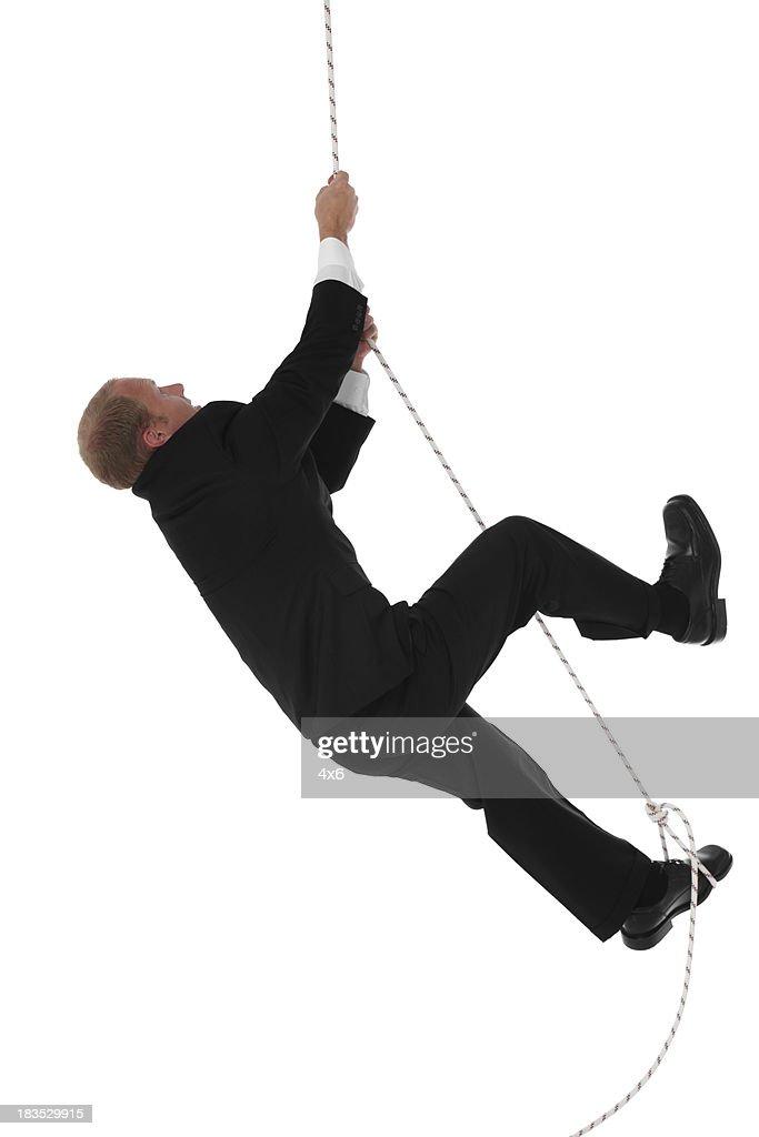 Businessman climbing rope