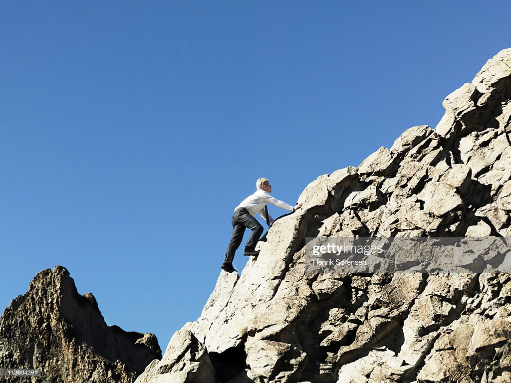 Businessman climbing up a mountain : Stock Photo