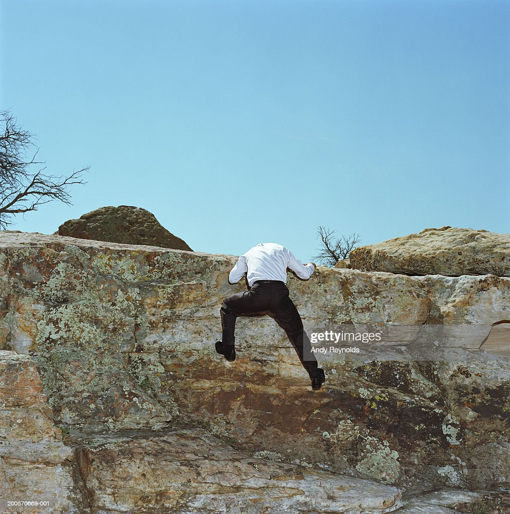 Businessman climbing up rock face in desert, rear view : Stock Photo