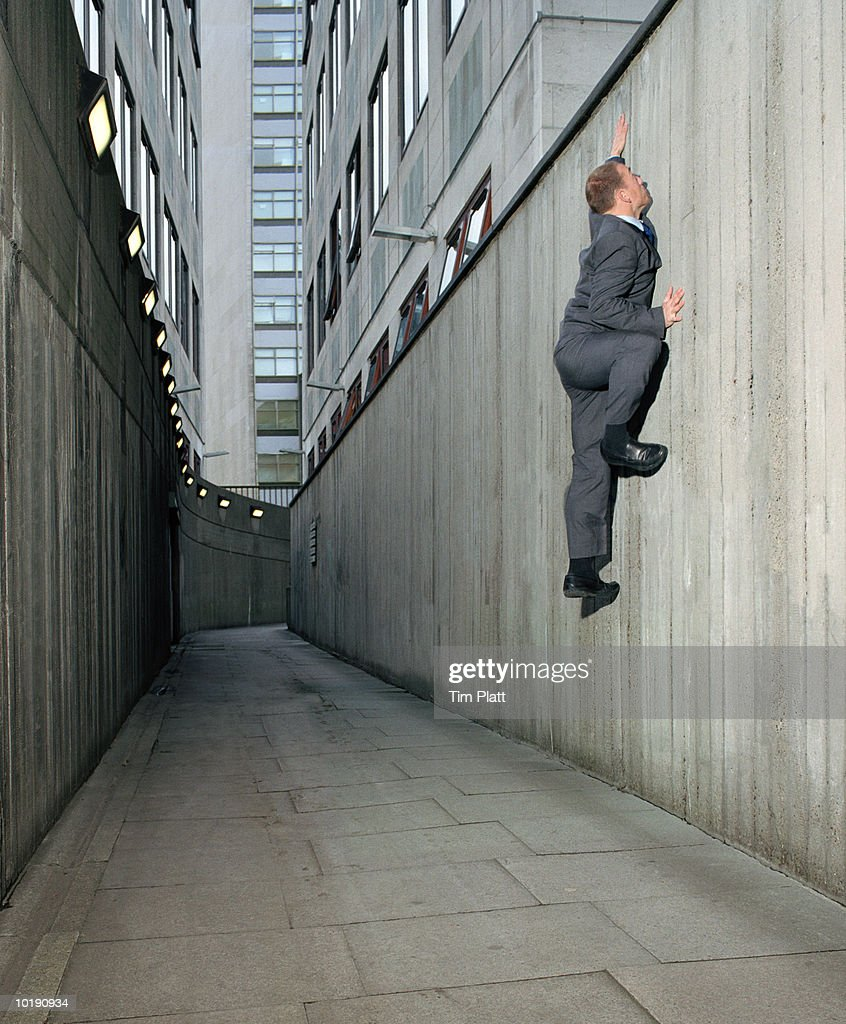 Businessman climbing wall in alley