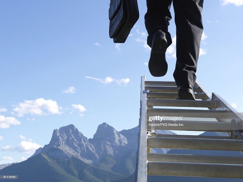 Businessman climbs ladder above mountains : Stock Photo