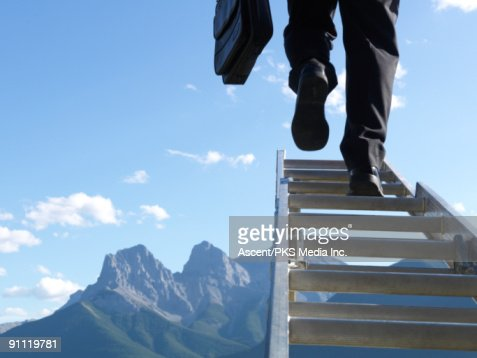 Businessman climbs ladder above mountains : Stock Photo