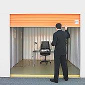 Businessman closing door of storage unit office