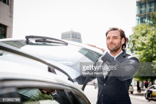 Businessman closing trunk of his car.