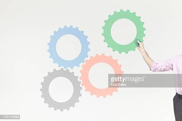 A businessman completing a system of cogs.