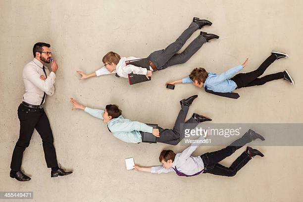 Businessman confused while boys in mid air