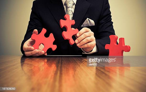Businessman connect two large jigsaw pieces
