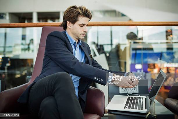 Businessman connecting plug to laptop at airport lobby