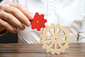 Businessman connects a small red gear to a large gear wheel. Symbolism of establishing business processes and communication. Increase efficiency and productivity. The best business formula for success