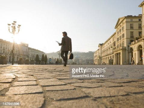 Businessman consults digital tablet,crosses piazza : Stock Photo