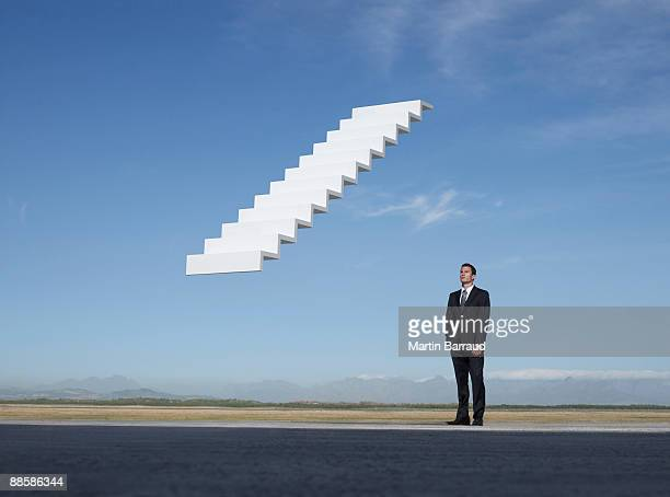 Businessman contemplating stairway to the sky