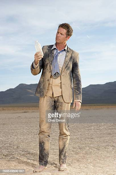 Businessman covered in dust holding empty water bottle