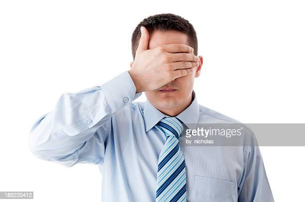 Geschäftsmann auf seine Augen mit hand, isoliert auf weiss