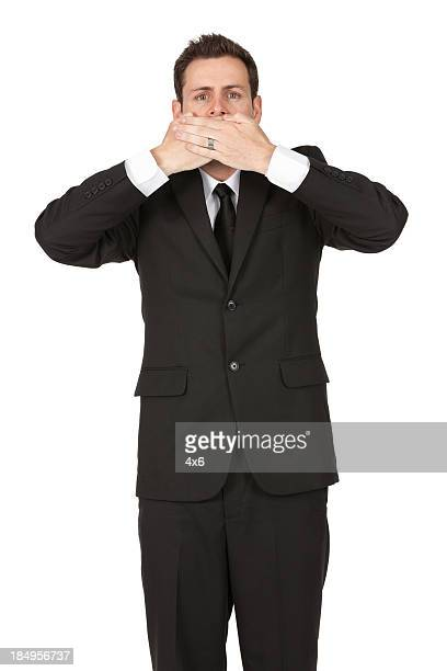 Businessman covering his mouth with hands